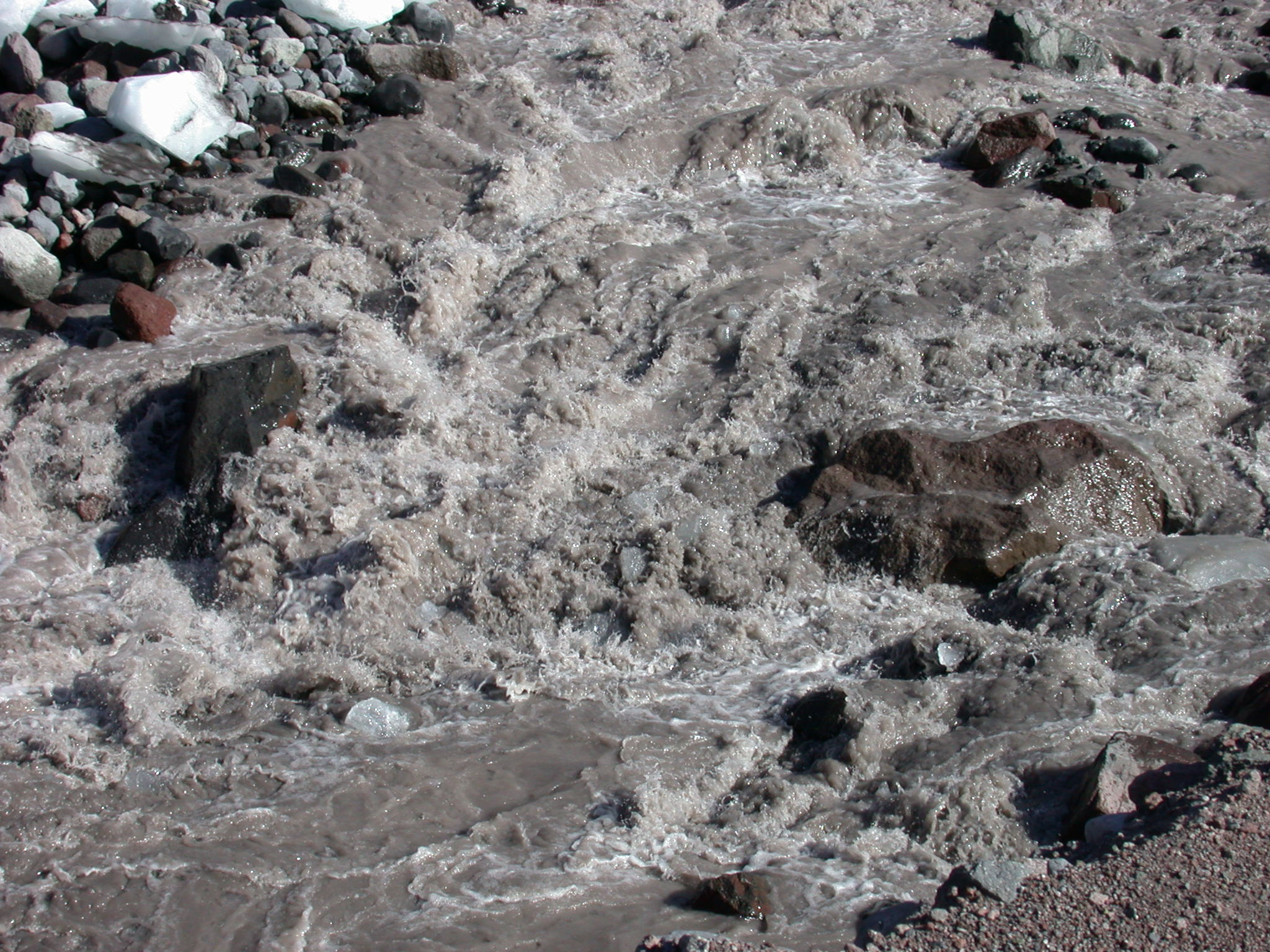 Ice Boulders Flowing in Glacial River Under Collapsed Ice Cave at Base of Glacier on Mount Rainier