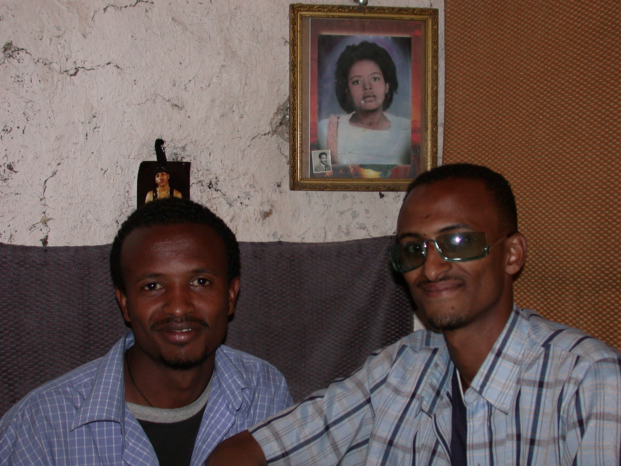 Paulos and Abdela Assiz in Front of Mother and Father Pictures at Paulos Apartment, Addis Ababa, Ethiopia