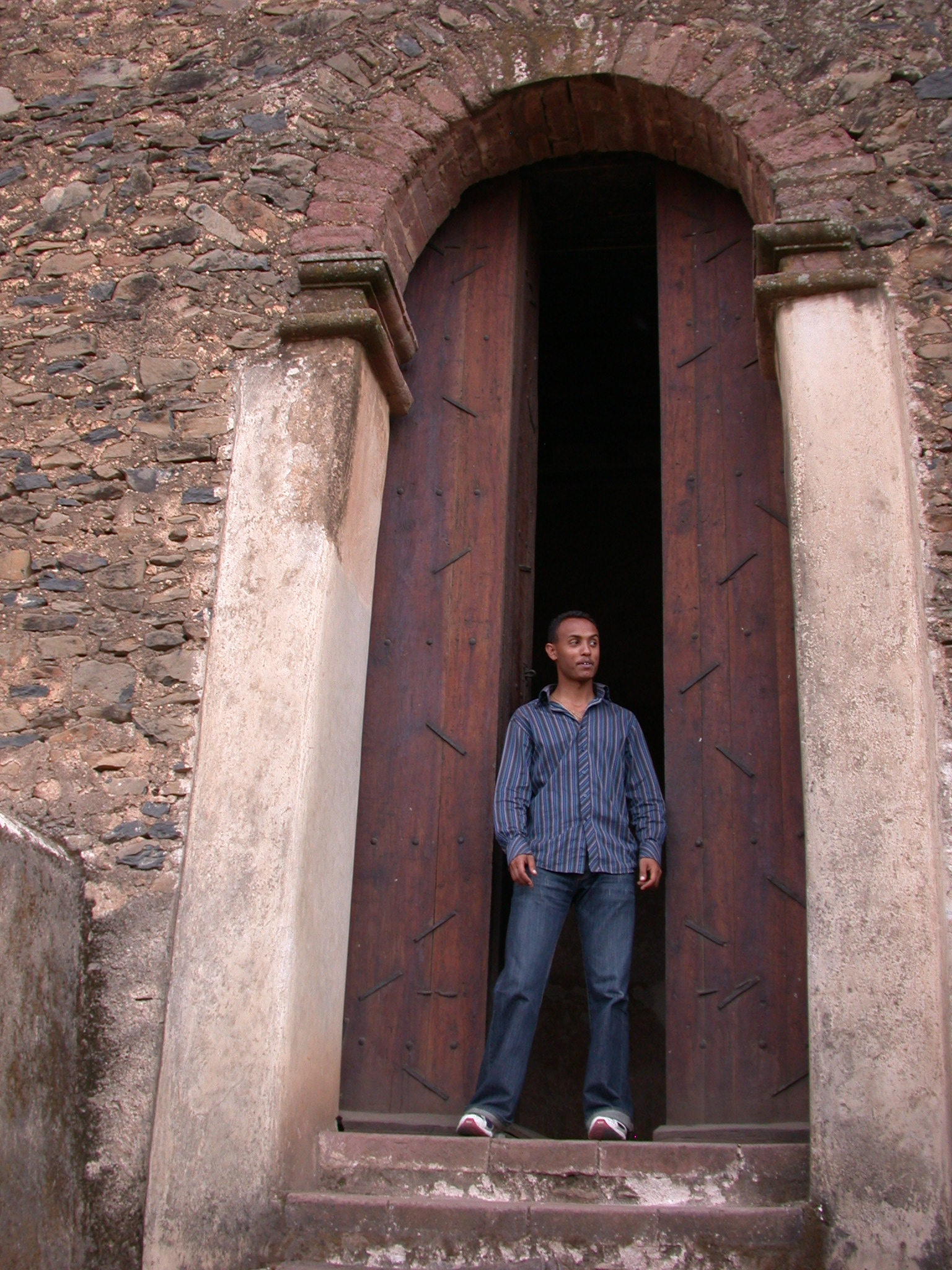 Ethiopian Friend in Front of Wooden Palace Door, Fasil Ghebbi Royal Enclosure, Gonder, Ethiopia