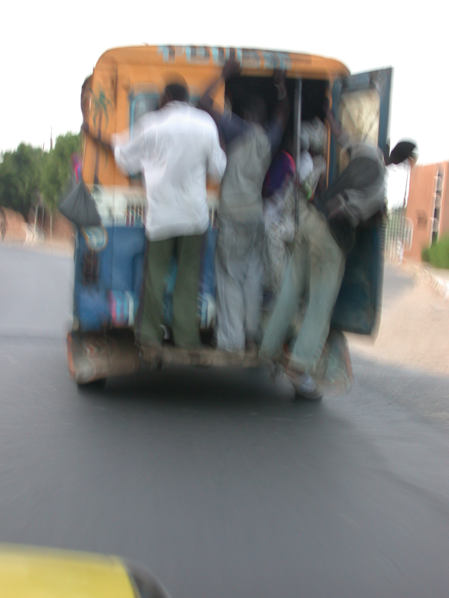 Guys Hanging Out of Elhamdulilah Bus in Dakar, Senegal