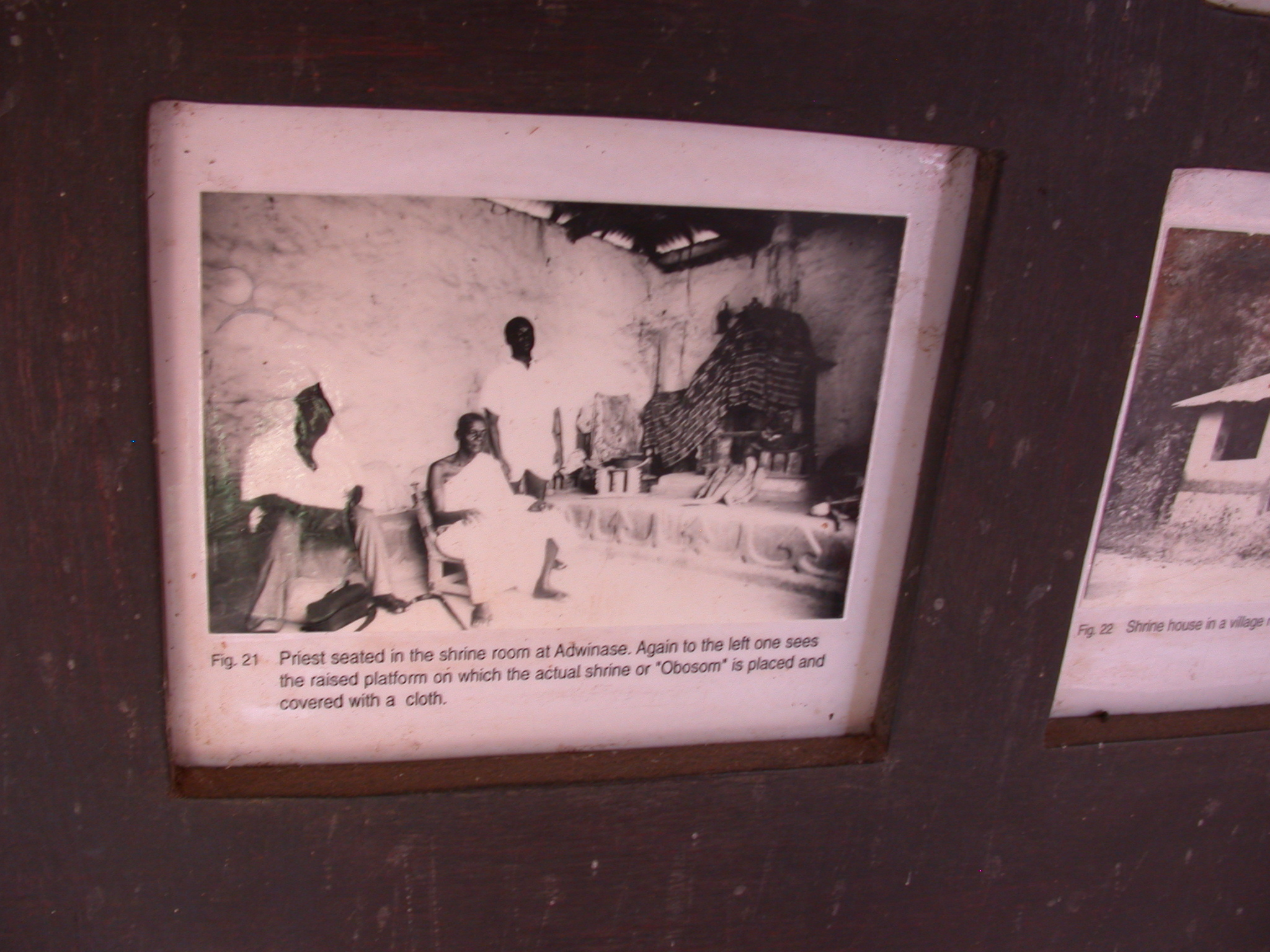 Photograph of Priest Seated in Shrine Room at Adwinase Shrine House With Obosom Shrine Covered by Cloth on Raised Platform, Asante Traditional Shrine at Ejisu-Besease, Ghana