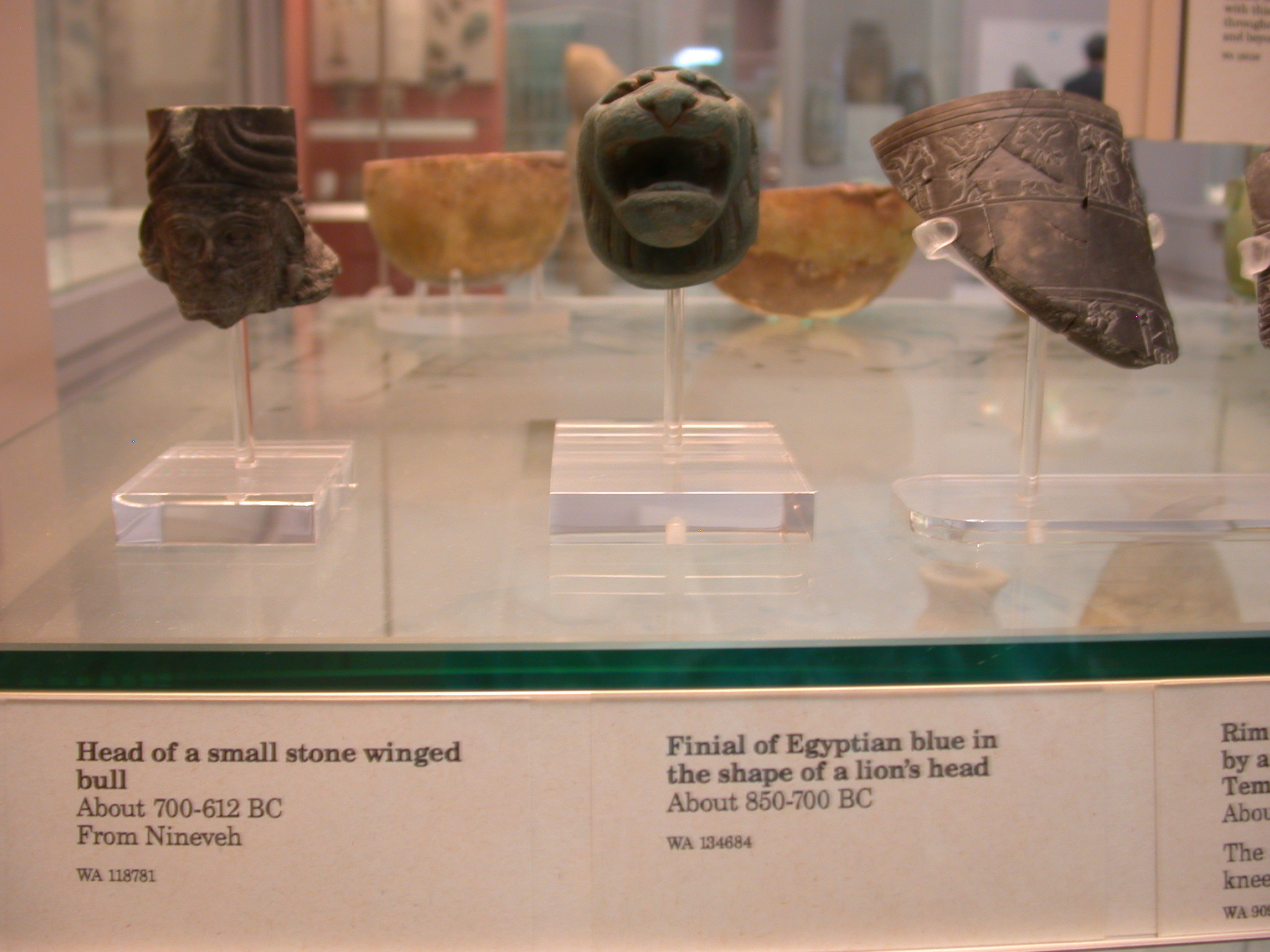 Head of Small Winged Bull, Stone, 700-612 BCE, Nineveh, Assyria, and Finial in Shape of Lion Head, Egyptian Blue, About 850-750 BCE, Assyria, in British Museum, London, England
